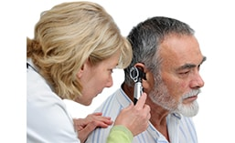 audiologist performing hearing test on male patient