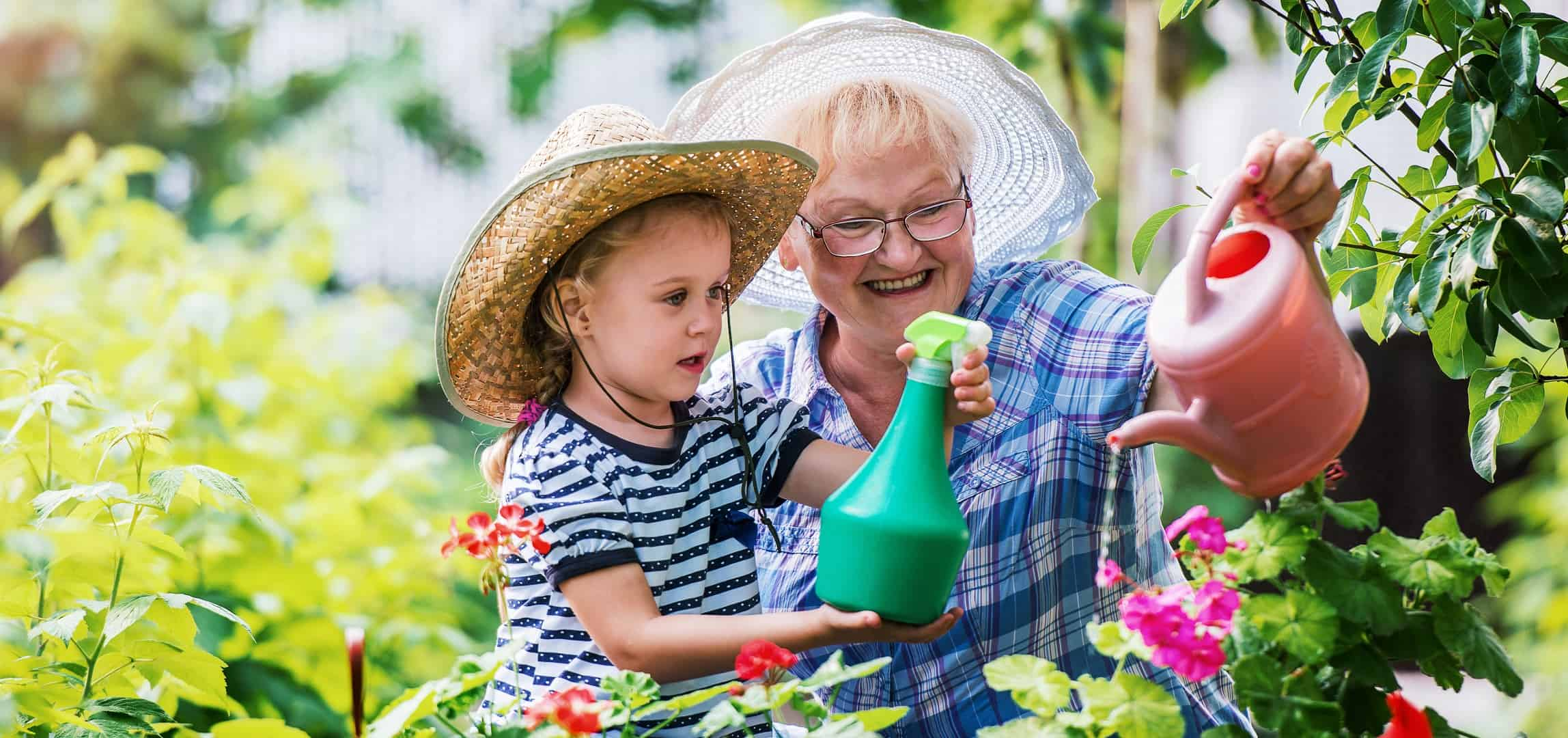 Image of grandmonther and granddaughter watering garden